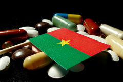 Burkina Faso flag with lot of medical pills isolated on black ba. Ckground Stock Photo
