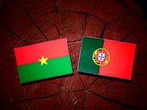 Burkina Faso flag with Portuguese flag on a tree stump isolated. Burkina Faso flag with Portuguese flag on a tree stump stock illustration