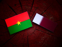Burkina Faso flag with Qatari flag on a tree stump isolated. Burkina Faso flag with Qatari flag on a tree stump Stock Images