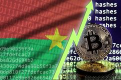Burkina Faso flag and rising green arrow on bitcoin mining screen and two physical golden bitcoins. Concept of high conversion in cryptocurrency mining royalty free stock photos