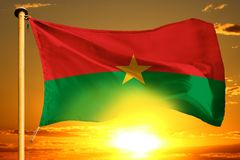 Burkina Faso flag weaving on the beautiful orange sunset with clouds background. Burkina Faso flag weaving on the beautiful orange sunset background stock photo