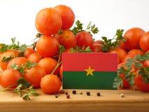 Burkina Faso -Flagge auf einer Holzverkleidung mit den Tomaten lokalisiert auf a Lizenzfreies Stockfoto