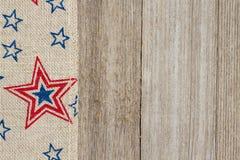 Burlap ΑΜΕΡΙΚΑΝΙΚΩΝ κόκκινη και μπλε αστεριών κορδέλλα στο ξεπερασμένο ξύλο backgroun Στοκ Εικόνες