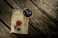 Burlap σάκος που βρίσκεται πέρα από το αγροτικό κατασκευασμένο ξύλινο γραφείο με το βάζο γυαλιού Στοκ Εικόνες