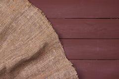 Burlap σύσταση στο ξύλινο επιτραπέζιο υπόβαθρο Στοκ Φωτογραφία