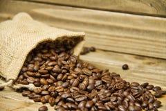 Burlap τσάντα των φασολιών καφέ που ανατρέπονται επάνω σε έναν ξύλινο πίνακα Στοκ φωτογραφία με δικαίωμα ελεύθερης χρήσης
