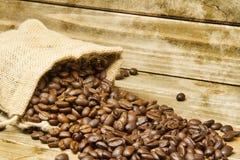 Burlap τσάντα των φασολιών καφέ που ανατρέπονται επάνω σε έναν ξύλινο πίνακα Στοκ φωτογραφίες με δικαίωμα ελεύθερης χρήσης