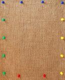 Burlap υπόβαθρο με τις καρφίτσες ως πλαίσιο Στοκ Εικόνες
