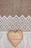 Burlap υπόβαθρο με το δαντελλωτός ύφασμα και την ξύλινη καρδιά Στοκ Εικόνες