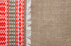 Burlap background bordered by country cloth. Burlap background bordered by red and green country cloth Royalty Free Stock Image