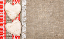 Burlap background bordered by country cloth and wooden hearts. Burlap background bordered by red and green country cloth and wooden hearts Royalty Free Stock Image