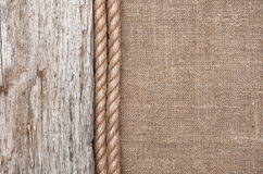 Burlap background bordered by rope and old wood Stock Image