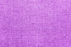 Burlap background colored in purple and white mix royalty free stock images