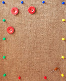 Burlap background decorated with pins, buttons and needle Royalty Free Stock Photography