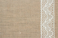 Burlap background. With lace ribbon Stock Image