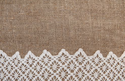 Burlap background with lacy cloth Stock Images