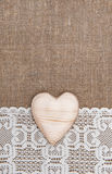 Burlap background with lacy cloth and wooden heart. Burlap background with white lacy cloth and wooden heart royalty free stock image