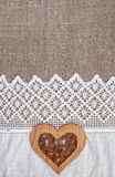 Burlap background with lacy cloth and wooden heart Royalty Free Stock Photography