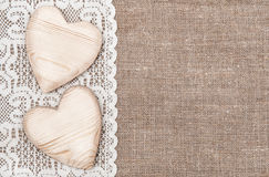 Burlap background with lacy cloth and wooden hearts Stock Photos