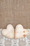 Burlap background with lacy cloth and wooden hearts. Burlap background with white lacy cloth and wooden hearts royalty free stock photos