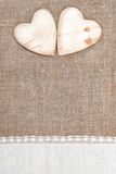 Burlap background with lacy cloth and wooden hearts. Burlap background with white lacy cloth and wooden hearts royalty free stock photo