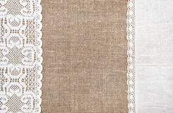 Burlap background with lacy and linen cloth. Burlap background with white lacy and linen cloth stock photos