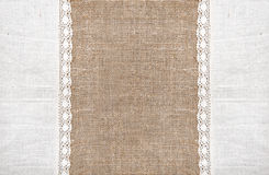 Burlap background with linen lacy cloth. Burlap background and white linen lacy cloth royalty free stock photography
