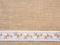 Burlap background with ribbon Royalty Free Stock Photography