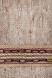 Burlap background with sacking ribbon, metal chain and rope Stock Photography