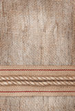 Burlap background with sacking ribbon and rope. Burlap textile background with sacking ribbon and rope stock photography