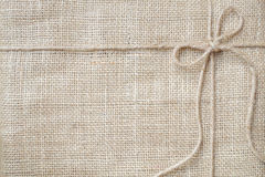 Burlap background tie with rustic burlap twine, natural product. Gift and eco-friendly concept royalty free stock photo