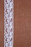 Burlap background - white lace. Background - brown color burlap hessian with white lace border royalty free stock image