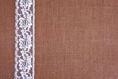 Burlap background - white lace. Background - brown color burlap hessian with white lace border stock image