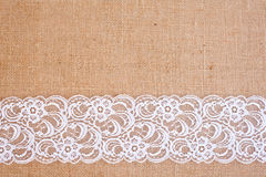 Burlap background - white lace. Background - natural color burlap hessian with white lace border stock photography
