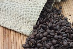Burlap Bag of Coffee Beans. A burlap or jute bag with roasted coffee beans on a bamboo mat Stock Image