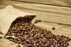 Burlap bag of coffee beans spilled onto a wood table. Royalty Free Stock Photo