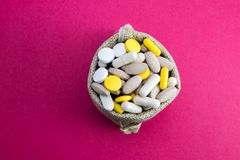 Burlap bag full of drug and medicine pills. top view. Paid medicine. Purchase of medicines pink background. Medicine and pharmacy royalty free stock images