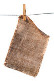 Burlap canvas with lacerate edges hanging. With wooden peg, isolated on white Stock Image