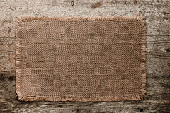 Burlap canvas with lacerate edges on old grunge. Wooden background Stock Photography