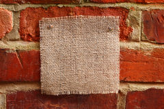 Burlap canvas with lacerate edges on red old. Brick wall Royalty Free Stock Photo