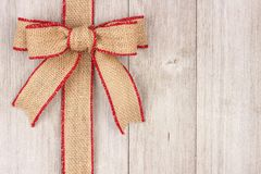 Burlap Christmas bow and ribbon side border on old white wood Stock Photos