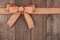 Burlap Christmas bow and ribbon top border on wood. Burlap Christmas bow and ribbon top border, above view on a rustic wood background Stock Photos