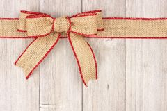 Burlap Christmas bow and ribbon top border on old white wood Stock Photography