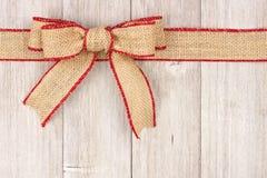Burlap Christmas bow and ribbon top border on old white wood. Burlap Christmas bow and ribbon top border, above view on an old white wood background stock photography