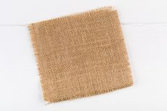 Burlap fabric cloth on white wooden kitchen table with copyspace. Burlap fabric cloth on white wooden kitchen table with copy space royalty free stock photography