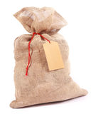 Burlap gift sack with a blank tag. Burlap gift sack with a blank label tag for your seasonal greeting tied with red string for a country Christmas, over white royalty free stock image