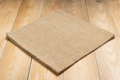 Burlap hessian sacking cloth on wooden table. Burlap hessian sacking cloth on wooden background table in front view royalty free stock photo