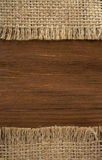 Burlap hessian sacking on wood Royalty Free Stock Photos