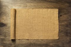 Burlap hessian on wooden background. Burlap hessian sacking on wooden background royalty free stock image