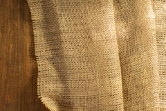 Burlap hessian sacking on wooden. Background royalty free stock photography
